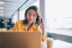 Positive female freelancer downloading media files during distance job with startup project using high speed internet connection on netbook, successful student preparing course work presentation