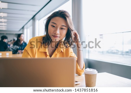 Positive female freelancer downloading media files during distance job with startup project using high speed internet connection on netbook, successful student preparing course work presentation #1437851816