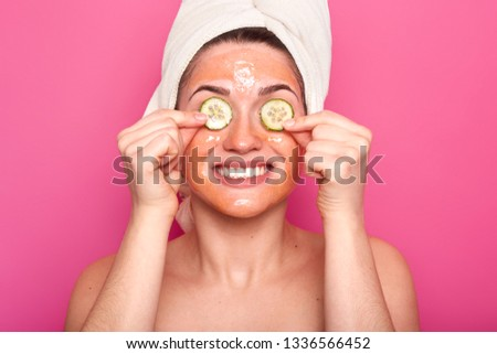 Positive female model pampers skin, applies beauty mask on face, has cucmber on eyes, smiles broadly, shows white teeth, poses bare shoulders, wears towel on head, isolated on pink background #1336566452