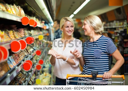 Positive female pensioner and her adult daughter choosing chilled sausages in shop