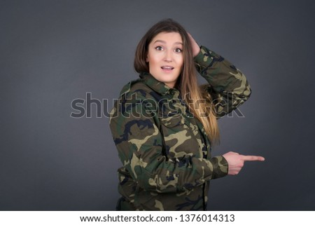 Positive female soldier says: wow how exciting it is, has amazed expression, indicates something. Joyful pretty young woman demonstrates something. One hand on her head and pointing with other hand.
