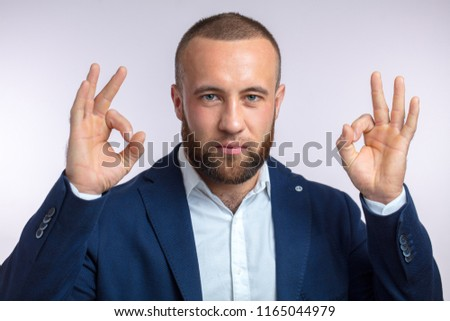 Positive financier in formal wear being glad and satisfied with favorable financial forecast gesturing at camera okey sign with both hands