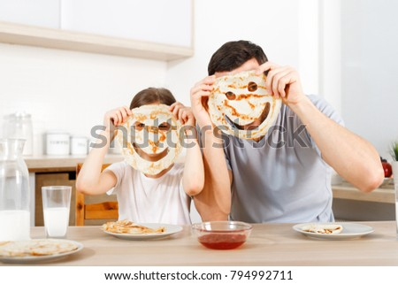Positive friendly daughter and father make funny faces from pancakes, looks through handmade eyes, sit at kitchen, have breakfast, wait for mother. People, relationship, culinary, family concpet.