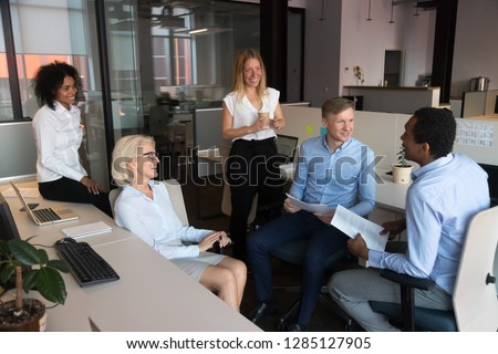 Positive friendly different ages and ethnicity coworkers communicating working brainstorming at coworking area, businesspeople reviewing document financial statistics feels happy discussing good news