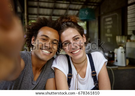 Positive friendly male and female from different countries rejoicing their meeting at cafe spending free time making photos of themselves having good mood. Happy mixed race couple making selfie