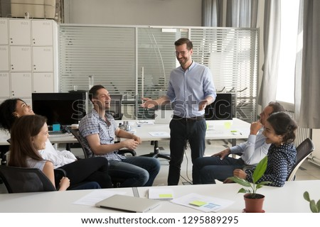 Positive friendly team leader or company owner talking with diverse multiracial workers during briefing in office. Coach helps employees improve develop their business skills for growing up in career