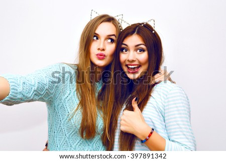Positive friends portrait of two happy sister girls making selfie, sure funny faces, grimaces,joy, emotions, casual style, pastel colors, white wall. Sending air kiss, and say ok.