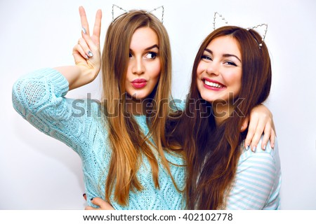 Positive friends portrait of two happy sister girls making selfie, sure funny faces, grimaces, joy, emotions, casual style, pastel colors, white wall. crazy funny woman.