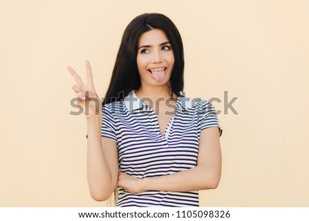 Positive funny female makes peace sign with hand, shows tongue, being in good mood, has long dark hair, has healthy skin, wears casual clothes, isolated over studio background. Body language #1105098326