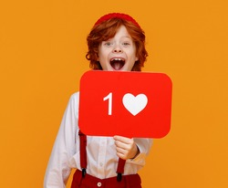 Positive ginger boy in stylish outfit demonstrating board with like symbol and looking at camera  while promoting social media against yellow background