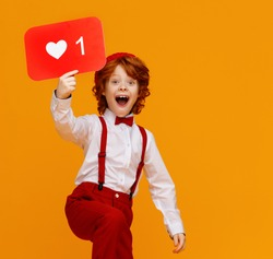 Positive ginger boy in stylish outfit demonstrating board with like symbol and looking at camera with opened mouth while promoting social media against yellow background