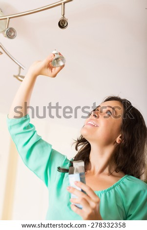 Positive girl changing light bulb at her home