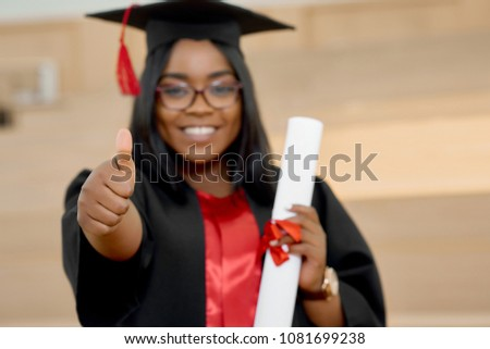 Positive girl graduating from university. Student wearing black and red education gown and keeping diploma.Standing in classroom with wooden cascade desks. Smiling, feeling happy. Blurred focus.
