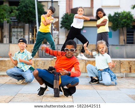 Positive girls and boys training hip hop on city street, outdoor dance class for kids Stockfoto ©