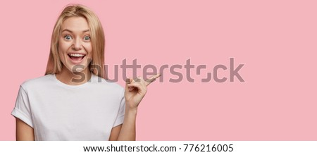 Positive glad female says: wow how exciting it is, has amazed expression, indicates at blank copy space for your advertisment or promotional content. Joyful pretty young woman demosntrates something