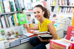 Positive glad woman taking literature books in store with prints