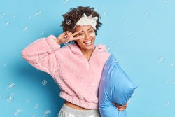 Positive good looking curly haired woman makes victory gesture over face smiles broadly wears comfortable clothes prepares for sleep isolated over blue background with soap bubbles. Rest concept