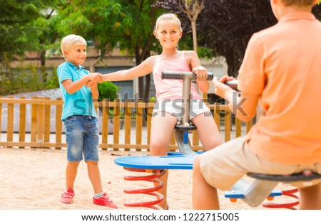 Stock Photo Positive greek children are teetering on the swing in the playground.