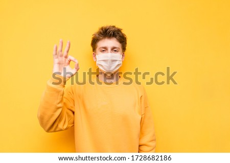 """Positive guy in a medical mask isolated on a yellow background, looks at the camera with a smile and shows a OK gesture. Cheerful guy in quarantine wears a mask and shows a """"okay"""" gesture"""