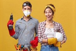 Positive handyworkers wearing casual protective clothes holding builduing equipment smiling sincerely while standing against yellow background. Maintenance workers being glad to finish their work