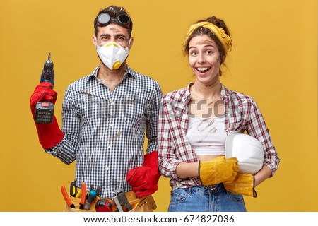 Positive handyworkers wearing casual protective clothes holding builduing equipment smiling sincerely while standing against yellow background. Maintenance workers being glad to finish their work Stock photo ©
