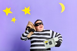positive happy burglar has stolen money from safe.happu man looking up, enjoying good day for crime
