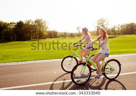 positive happy girls in love ride bicycles on the park