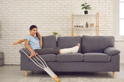 Positive happy young woman with broken leg in plaster cast sitting on sofa with crutches at home, talking on mobile phone, telling friend or relative about accident which resulted in bone fracture
