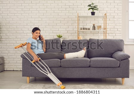 Positive happy young woman with broken leg in plaster cast sitting on sofa with crutches at home, talking on mobile phone, telling friend or relative about accident which resulted in bone fracture ストックフォト ©