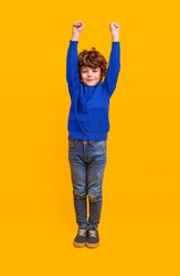 Positive healthy little boy with curly hair dressed in casual blue sweatshirt and jeans keeping hands up and looking at camera isolated against yellow background