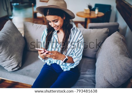 Positive hipster girl in stylish hat chatting on internet website on modern mobile phone connected to free 4G internet.Cheerful blogger sending sms messages on smartphone resting in coffee shop #793481638