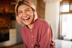 Positive human emotions and facial expression. Attractive casually dressed young female in her twenties burst out laughing, expressing genuine reaction, having fun in stylish cozy apartment