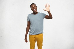 Positive human emotions, facial expressions, feelings, attitude and reaction. Friendly-looking polite young African American man dressed in grey t-shirt and mustard jeans saying hi, waving his hand