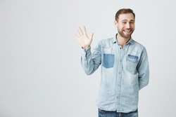 Positive human emotions, facial expressions, feelings, attitude and reaction. Friendly-looking polite young European man dressed in denim shirt and jeans saying hi, waving with his hand