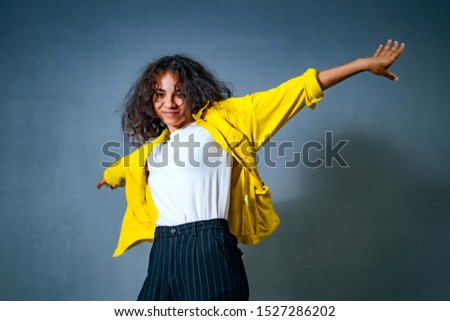 Positive human emotions. Headshot of happy emotional teenage girl bob curly haircut with spreaded hands, wearing bright makeup.. Wearing bright yellow cotton jachet and white shirt. Blue background.