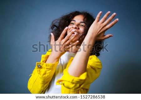 Positive human emotions. Headshot of happy emotional teenage girl with bob curly haircut with hands on the front, wearing bright makeup. Wearing bright yellow cotton jachet and white shirt.