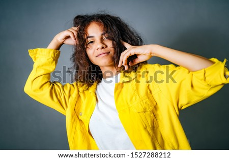 Positive human emotions. Headshot of happy emotional teenage girl with bob curly haircut with hands near the ear and a head, wearing bright makeup. Blue background.