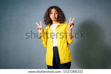 """Positive human emotions. Headshot of happy emotional teenage girl with bob curly haircut with hands making """"peace"""" sign, wearing bright makeup. Blue background. Wearing bright yellow cotton jachet and"""