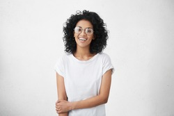 Positive human facial expressions and emotions. Isolated shot of attractive dark-skinned student girl in round eyewear looking and smiling broadly at camera during nice conversation with someone