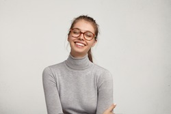 Positive human facial expressions, emotions, reaction and feelings. Fashionable cheerful young female in eyewear closing eyes, laughing from the bottom of her heart, holding hands on stomach