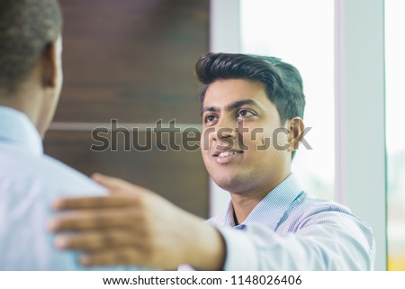 Positive Indian professional congratulating colleague on success. Closeup of smiling Indian office worker keeping hand on colleague shoulder in support gesture. United team concept