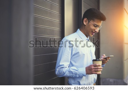 Positive indu student in casual wear watching funny video and messaging with friends in online chat on mobile phone using 4G internet connection standing outdoors near promotional background Zdjęcia stock ©