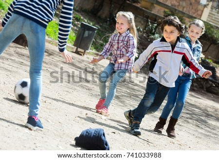 Positive junior school girls and boy playing street football #741033988