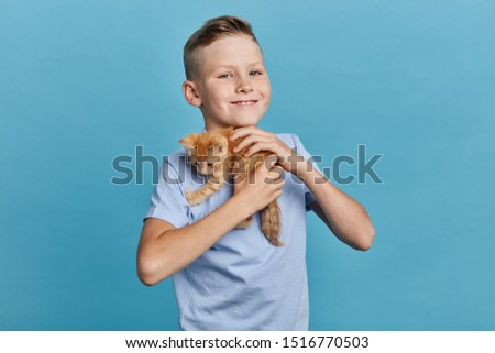 positive kid embracing his orange kitten and looking at the camera, close up portrait, animal lover