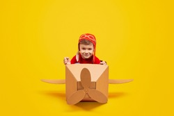 Positive kid in aviator hat looking at camera and smiling while flying in carton aircraft against bright yellow background