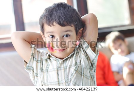 Positive kid with colors on his face and body