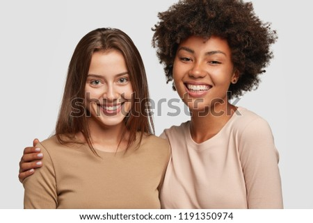 Positive ladies of different races stand next to each other, have warm hug, pleasant smile, friendly relationships, isolated over white background. Diverse women pose for making company photo
