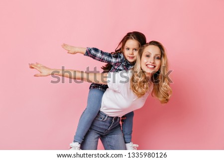 Positive lady and her daughter play, imagining themselves to be airplanes. Curly blonde woman holding baby on her back on pink background #1335980126
