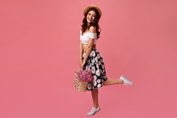 Positive lady in bright outfit smiles and poses with pink flowers. Beautiful red-haired girl in yellow dress holds large bouquet and have fun
