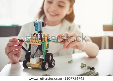 Positive lady playing with toy. She making it from constructor. Entertainment concept